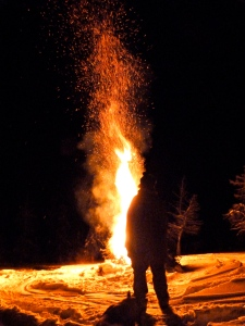 Ella chews a stick while Gary watches the bonfire